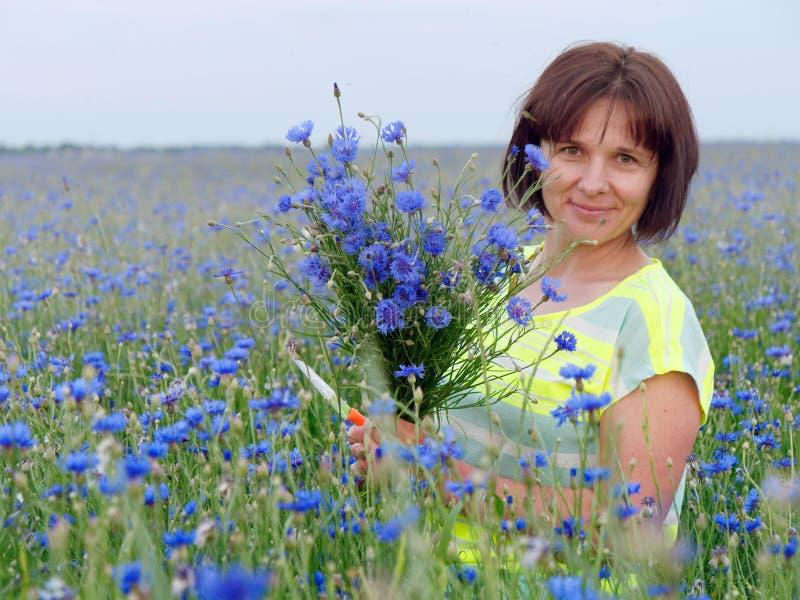 Chabrowy pole przy zmierzch dziewczyną z bukietem fotografia royalty free