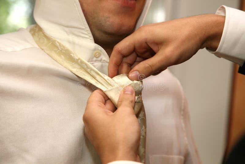 Chacun aide à porter la cravatte au marié photos stock