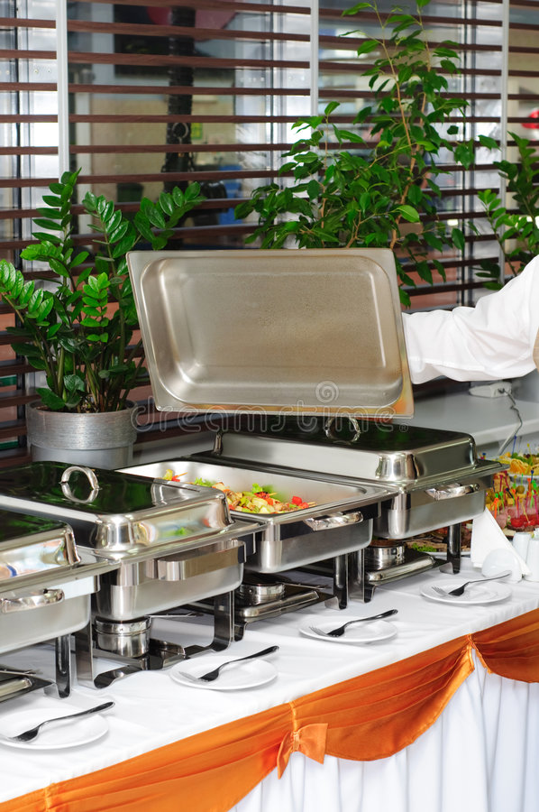Chafing dish heater with fish kebab. Chafing dish heater filled with ready grilled fish kebab stock image
