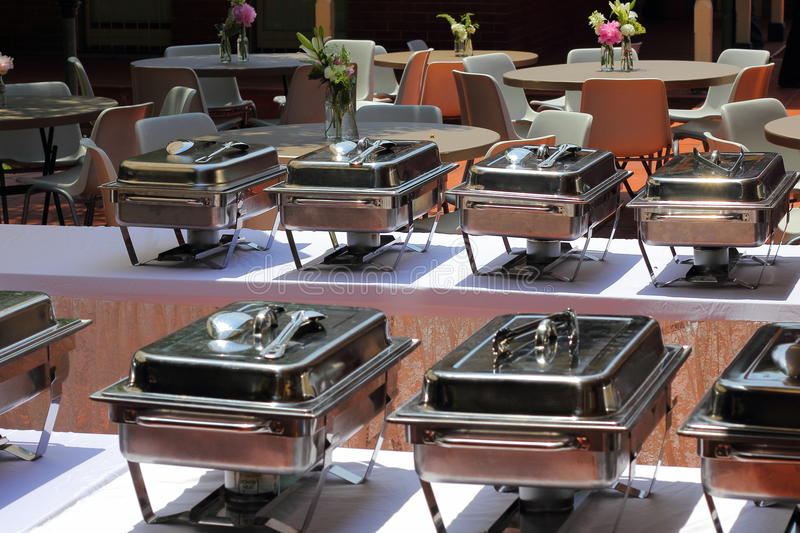Chafing dishes banquet table. An array of Chafing dishes - readily prepared for a banquet in a hall with tables in the background stock photo