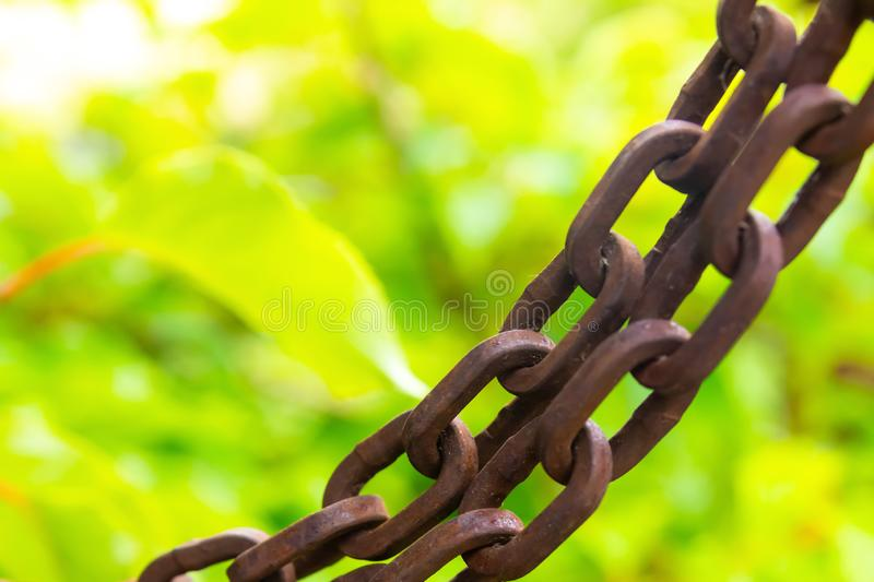 Chain brown long old rusty on a blurry background light green grunge design royalty free stock photo