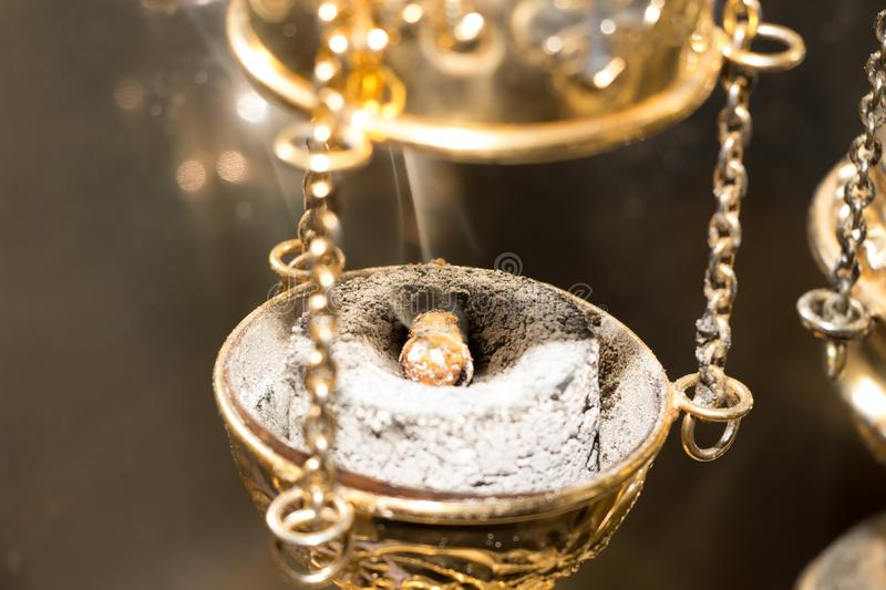 Chain censer with incense on burning charcoal. Golden chain censer with incense on burning charcoal. Close-up. During divine liturgy in Eastern Church. White stock photos
