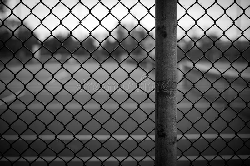 Chain Link Fence Background. Black and white chain link fence background image with background blurred in a shallow depth of field stock image