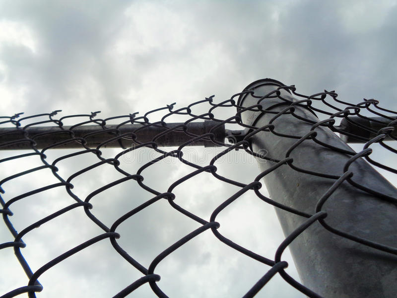 Chain Link Fence Barrier. This is an image looking up at storm clouds breaking up through a chain link fence. This picture could represent challenges, hope stock image