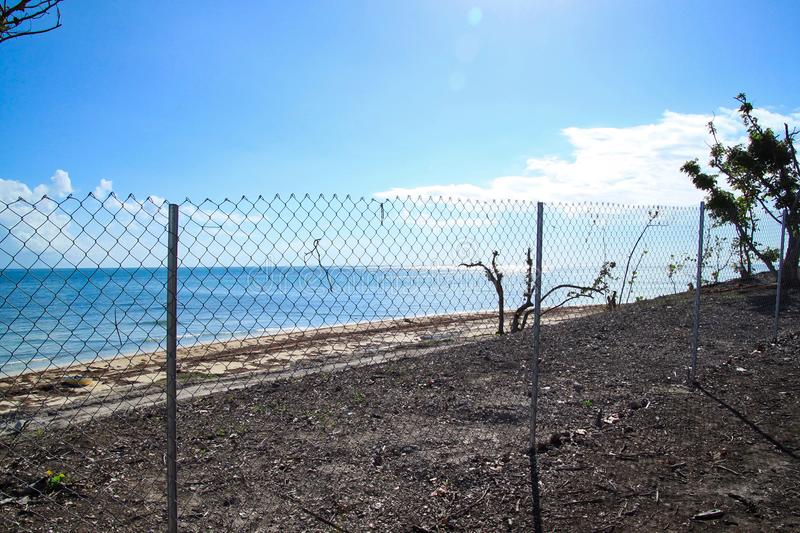 Chain link fence blocking off recovering area of beautiful Florida Keys beach after being destroyed by Hurricane Irma in 2017. Chainlink fence blocks off royalty free stock photos