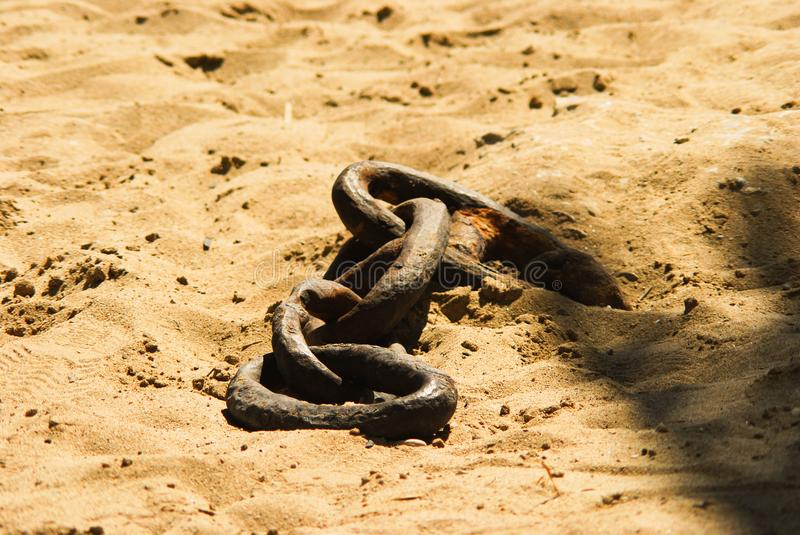 Chain links. Iron chain links on the sand of a beach stock images