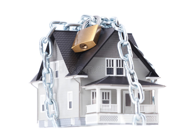 Chain with lock around the house. Real estate concept - chain with lock around the house architectural model, isolated royalty free stock photo