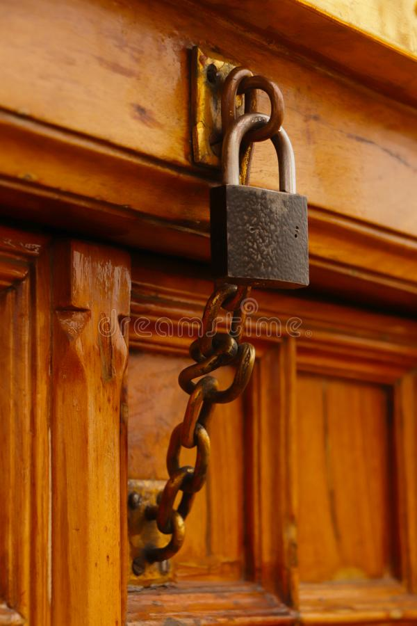 Chain with a lock. Bronzed chain lock on wooden door stock images