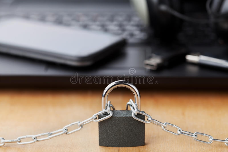 Chain with lock in front of the laptop and smartphone, gadget and digital devices detox concept. Chain with lock in front of laptop and smartphone, gadget and stock photos