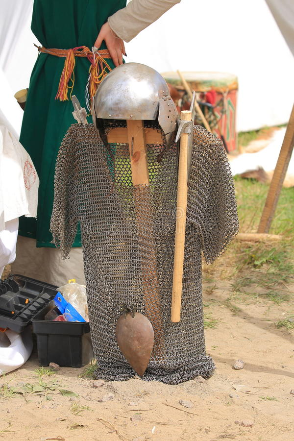 Chain mail, battle helmet and axes. Front view. Festival `Legends of the Norwegian Vikings`. Hare Island. Saint-Petersburg, Russia stock image