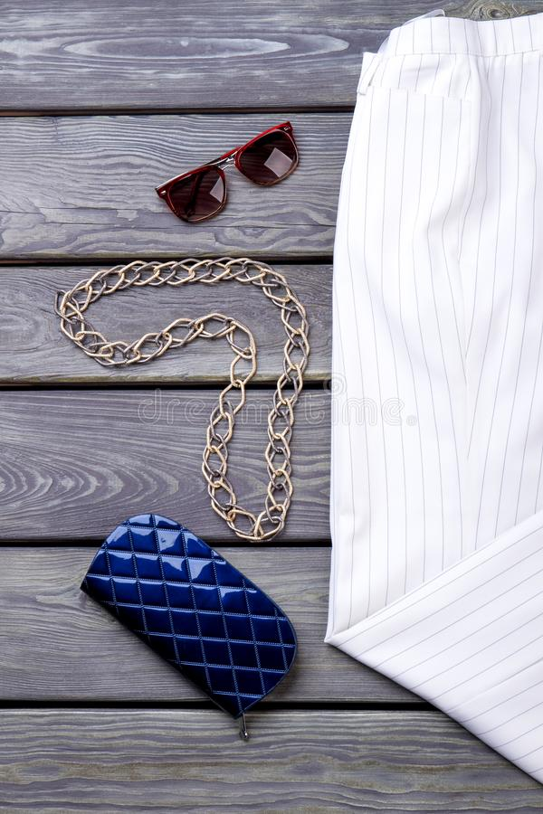 Chain necklace with sunglasses and blue wallet. royalty free stock photography