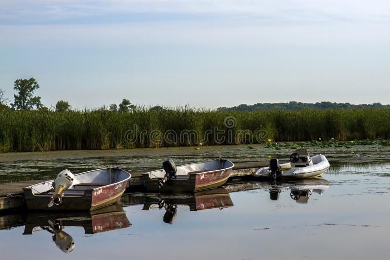 Fishing boats at Chain O` Lakes State Park. Three motorized fishing boats reflected in the water at dawn in Chain O` Lakes State Park near Antioch, Illinois royalty free stock images