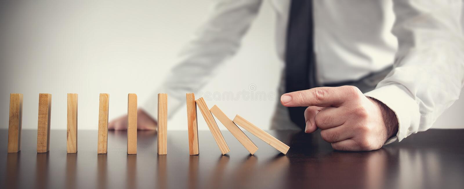 Chain Reaction In Business Concept, Businessman Just Starting Dominoes Toppling stock photography