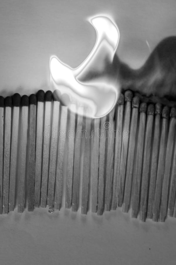 Chain reaction of matches B&W. Chain reaction of matches being ignited by each other in black and white colours royalty free stock images
