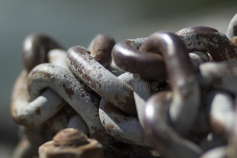 Chain with rusty thick links on a dock. Using bokeh stock images
