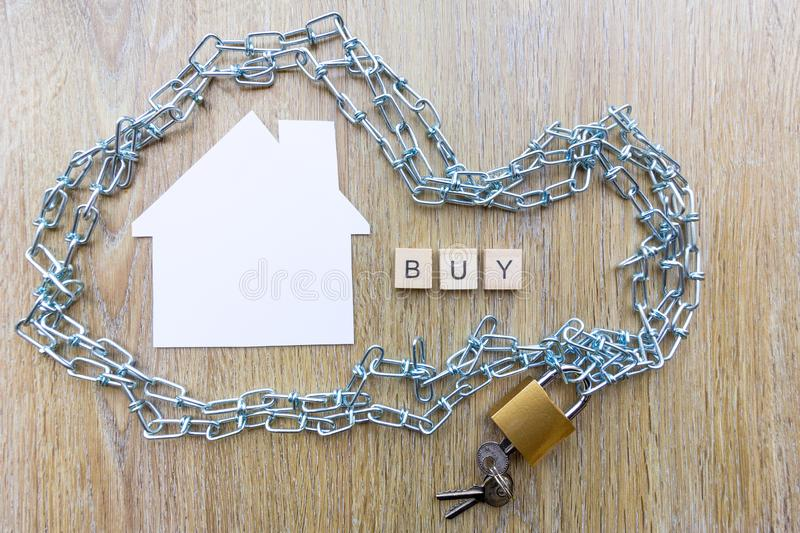 Chain surrounding a house with the word buy. Buying and debt concept - chain surrounding a house with the word buy royalty free stock photo