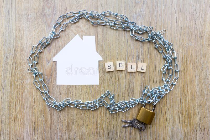 Chain surrounding a house with the word sell. Selling and debt concept - chain surrounding a house with the word sell stock photo