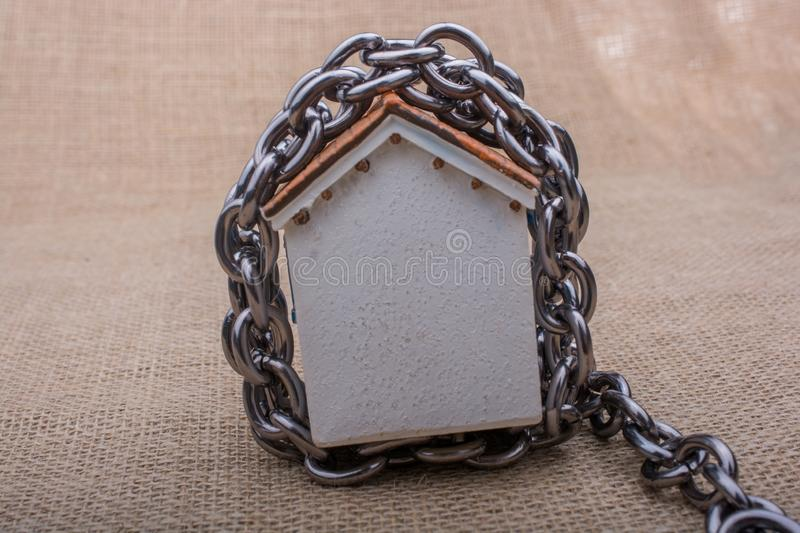 Chain wrapped around  a model house. On a brown background stock image