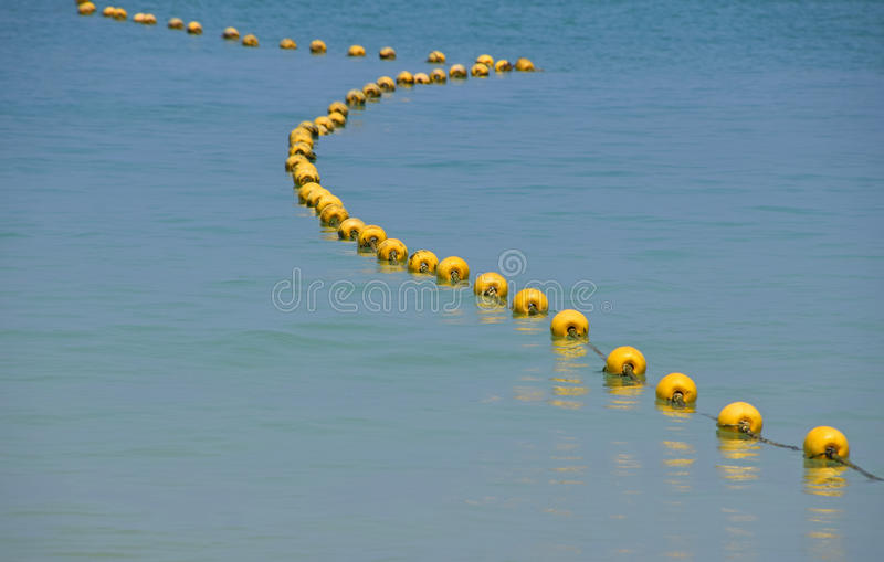Chain of yellow buoys in blue sea water stock photos