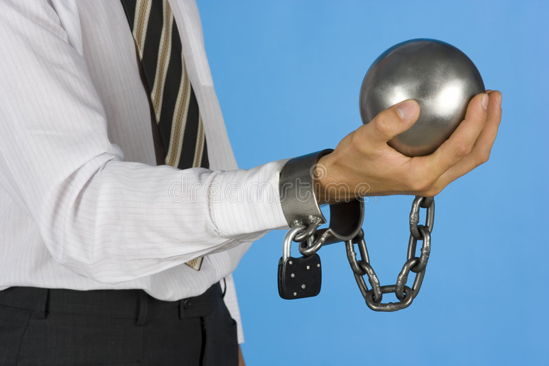 Chained businessman. Businessman with ball and chain on his hand royalty free stock photos