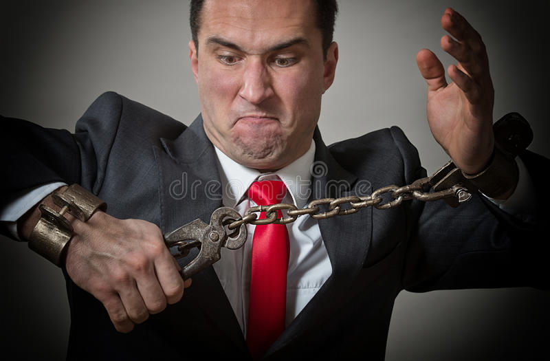 Chained businessman. Angry businessman breaking the shackles on his hands royalty free stock photo