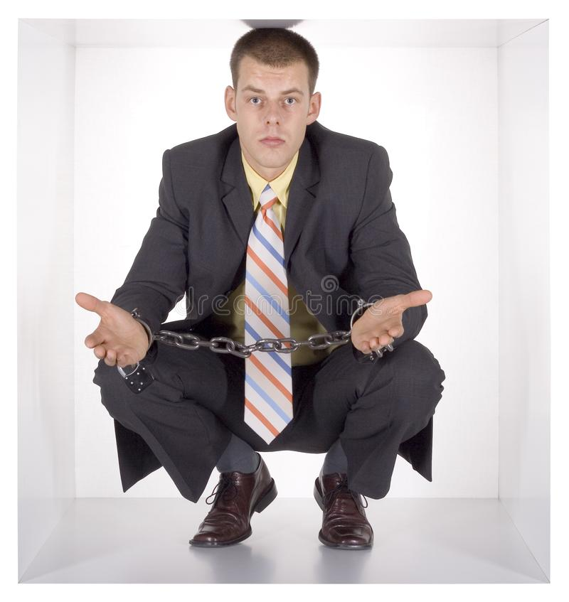 Chained businessman in the cube royalty free stock image