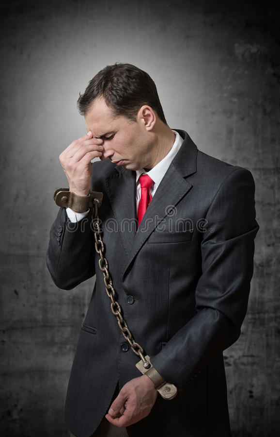Chained businessman. Depressed businessman with chained hands, studio shot royalty free stock images