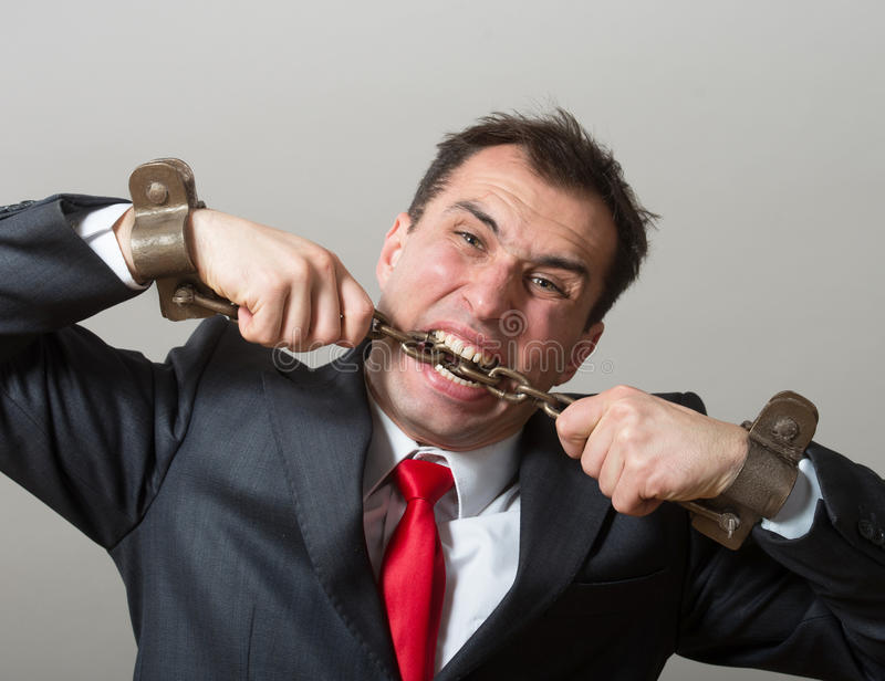 Chained businessman. Desperate businessman biting through the shackles on his hands stock image