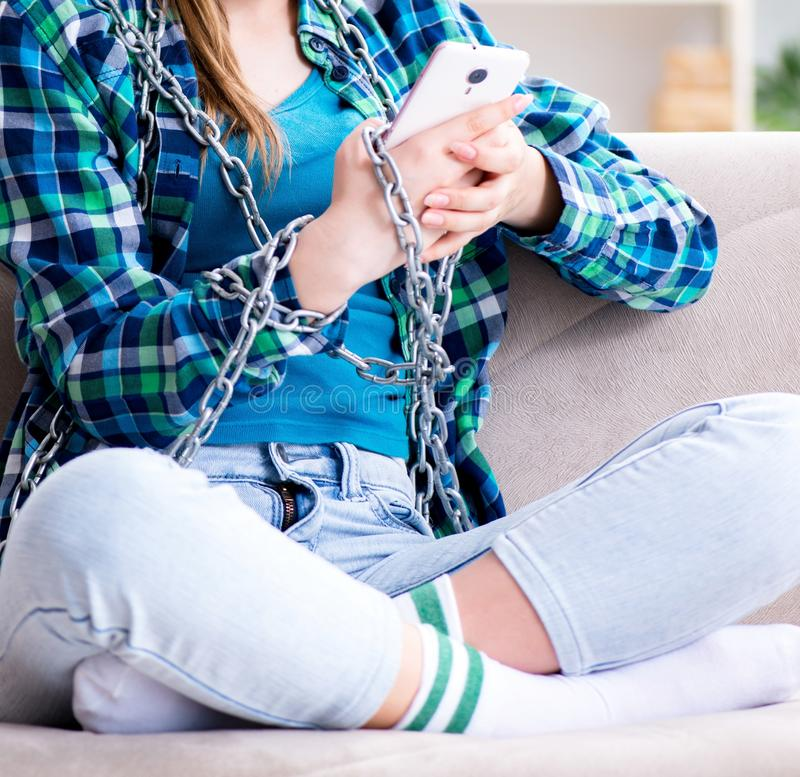 Chained female student with mobile sitting on the sofa royalty free stock photo