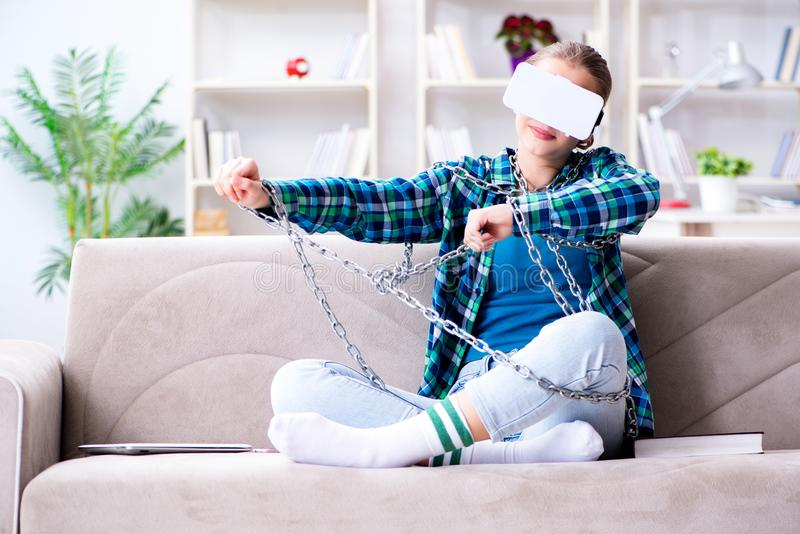 The chained female student with virtual glasses sitting on the sofa stock photo