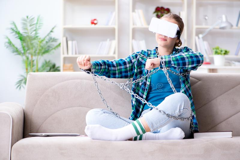 The chained female student with virtual glasses sitting on the sofa royalty free stock photos