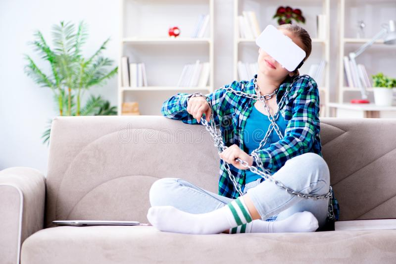 The chained female student with virtual glasses sitting on the sofa royalty free stock image