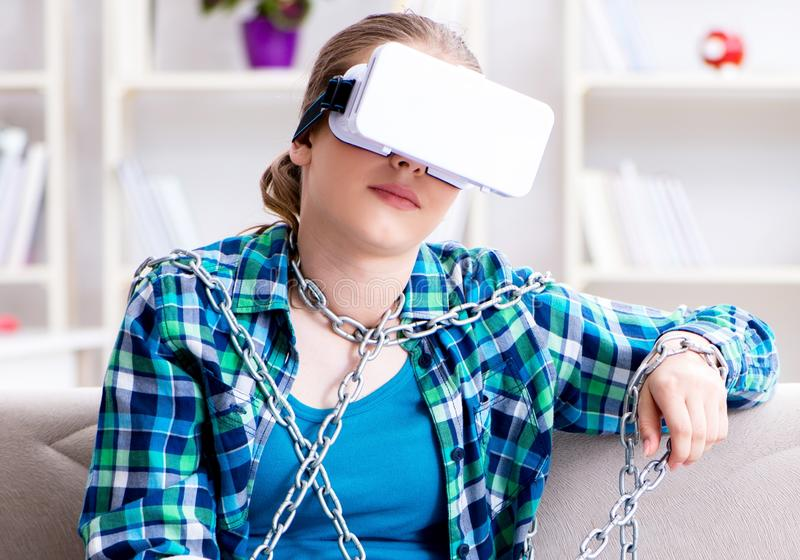 Chained female student with virtual glasses sitting on the sofa royalty free stock photos