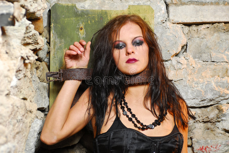 Chained Goth Girl. A goth girl chained on a stone wall in ruined premises royalty free stock photos