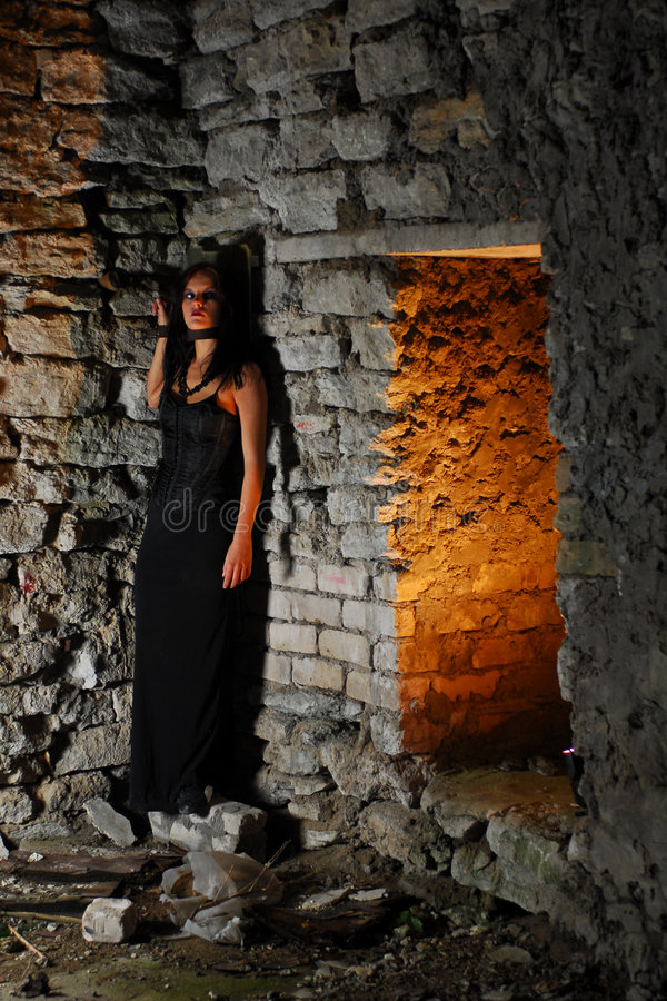 Chained Goth Girl. A dangerous goth girl chained on a stone wall in ruined premises at night stock photos