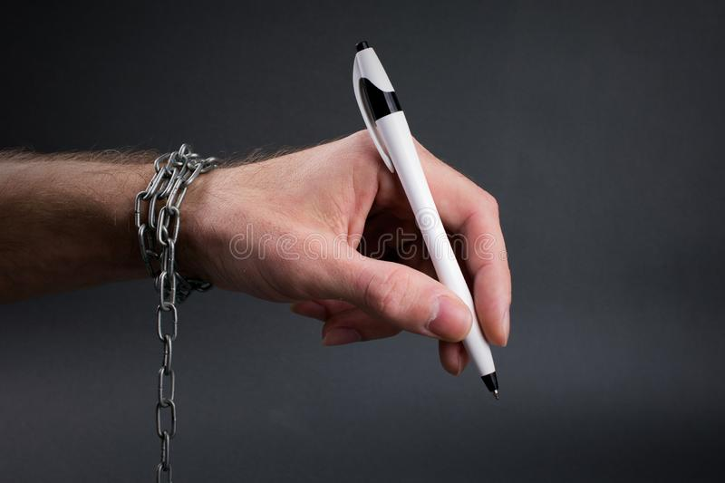 Chained hand holding  pen ready to sign. Enslavement concept, chained hand holding  pen ready to sign, close up, selective focus , blurred dark background royalty free stock photography