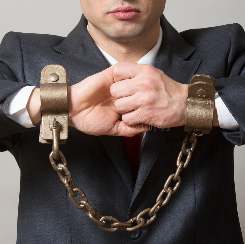 Chained hands. Linked male hands with the shackles, studio shot, gray background stock photo