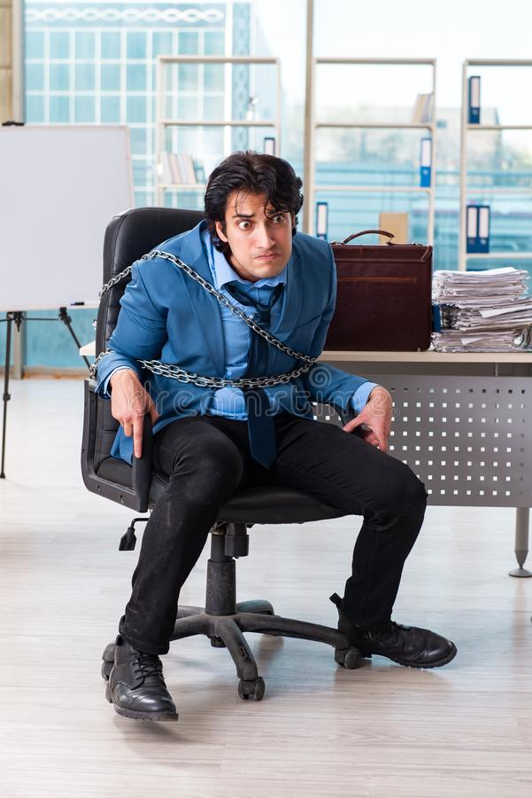 The chained male employee unhappy with excessive work royalty free stock photos