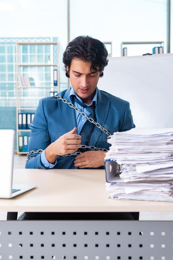 The chained male employee unhappy with excessive work royalty free stock photo