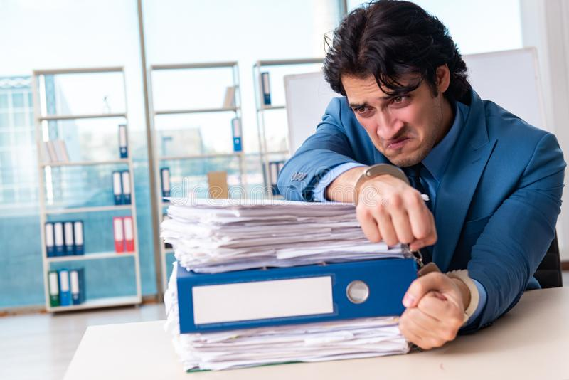 Chained male employee unhappy with excessive work royalty free stock images