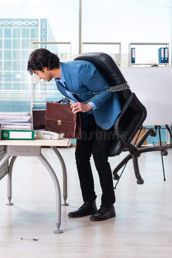 Chained male employee unhappy with excessive work stock photo