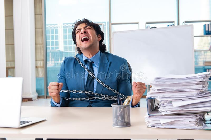 Chained male employee unhappy with excessive work royalty free stock photos