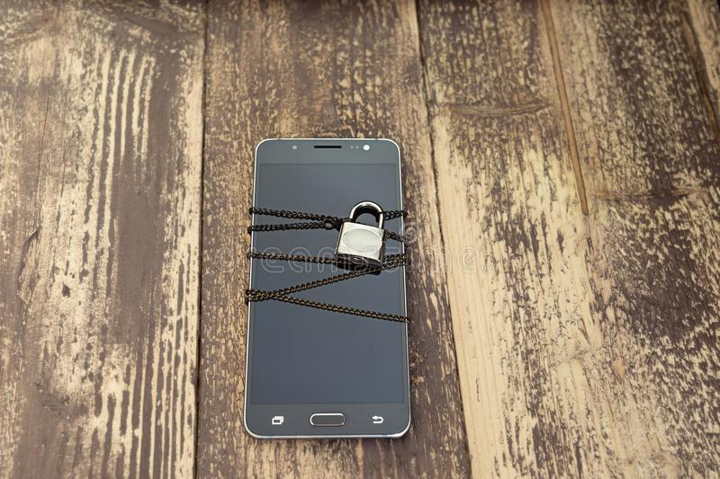A chained smartphone - data protection concept. Internet security smartphone data theft concept stock photography
