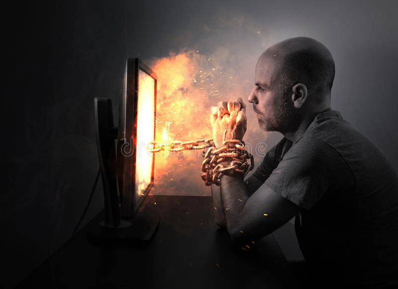 Chained to flaming computer royalty free stock image