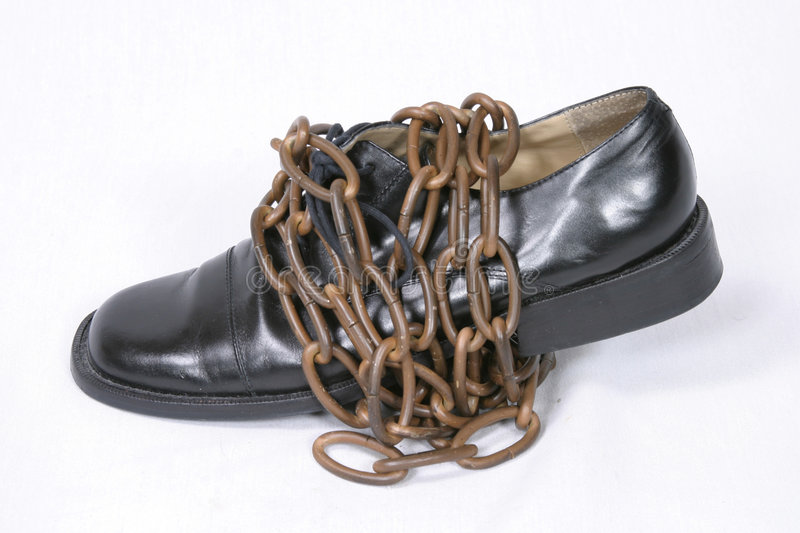 Chains That Bind. Black oxford dress shoe wrapped in bronze chain royalty free stock images