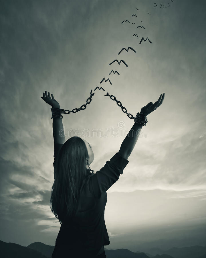 Chains and freedom. A woman breaks her chains as the links turn into freedom birds royalty free stock photography
