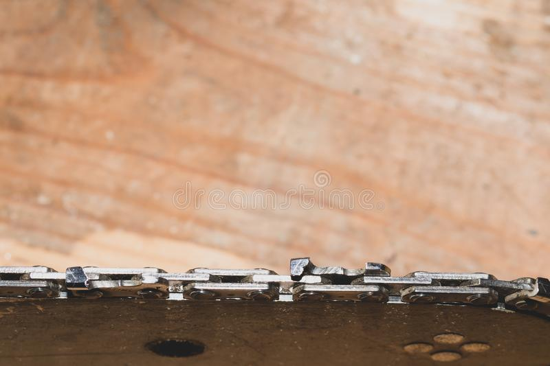 Chainsaw bar and cutting chain close up. blade of a chainsaw on a wooden background stock photos