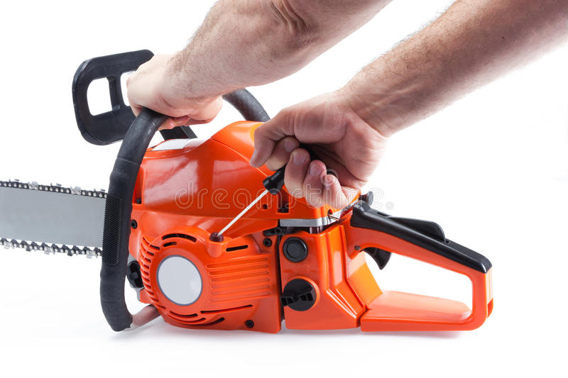 Chainsaw being started. By hand. chainsaw is orange in color and shot on a white background with a light drop shadow royalty free stock images