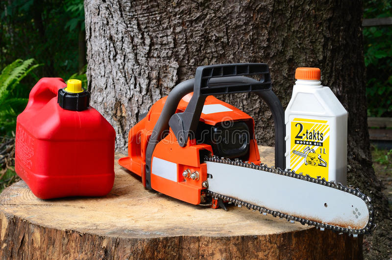 Chainsaw and canister of gasoline and motor oil stock photography