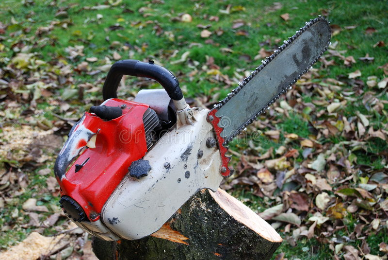 Chainsaw on cut tree stump. Old chainsaw on top of cut tree stump outdoors stock photos
